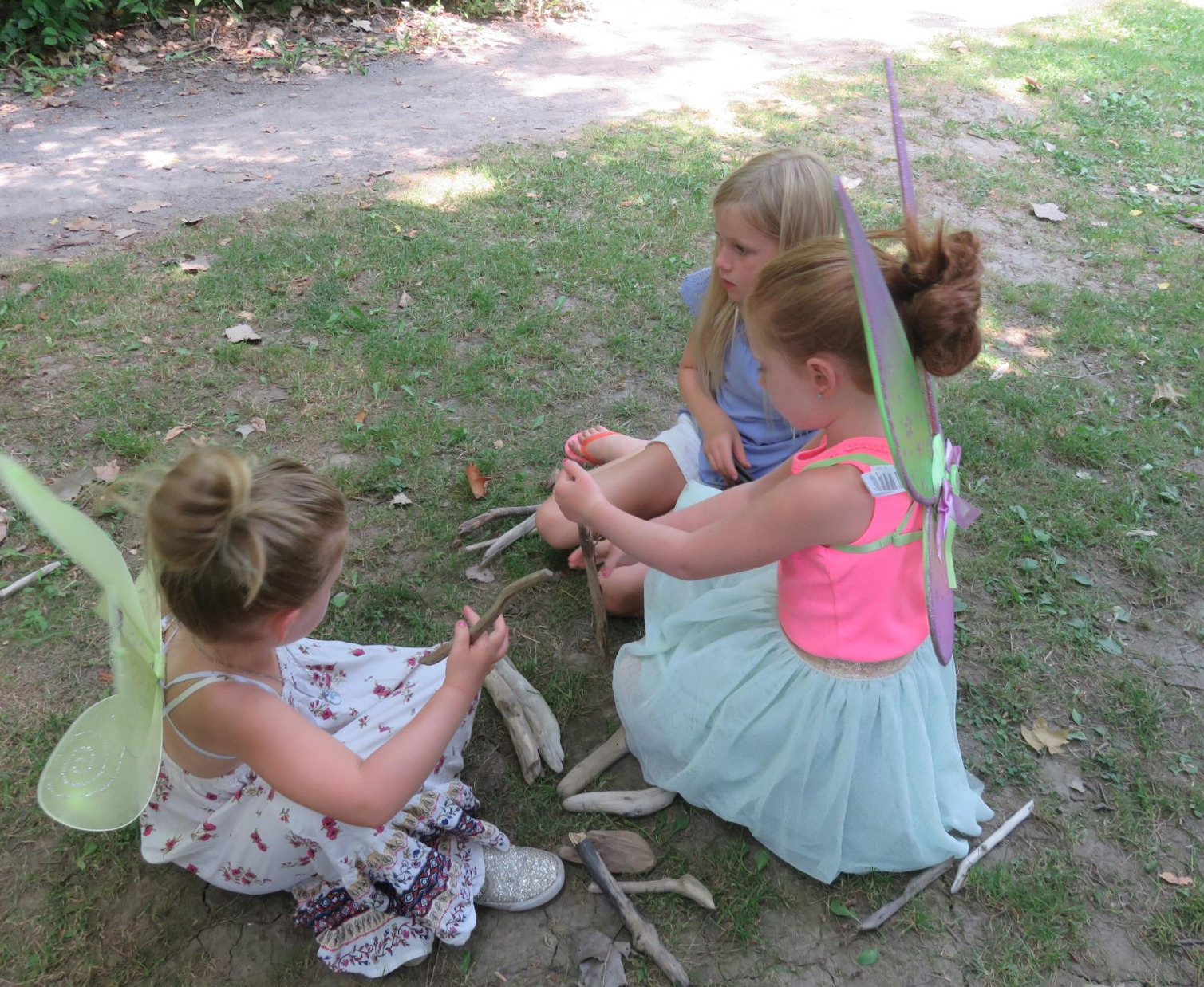 three young girls sitting on the ground in their fairy costumes working with sticks