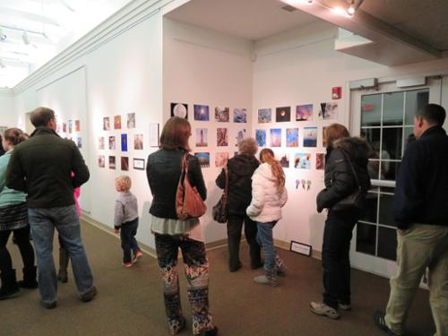 guests of all ages enjoying the photography competition gallery opening.