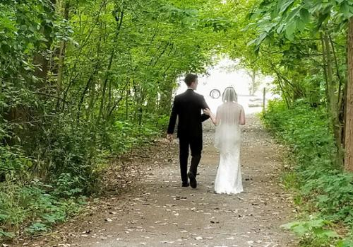 A couple walks through the natural arbor within the Burchfield Nature Center.